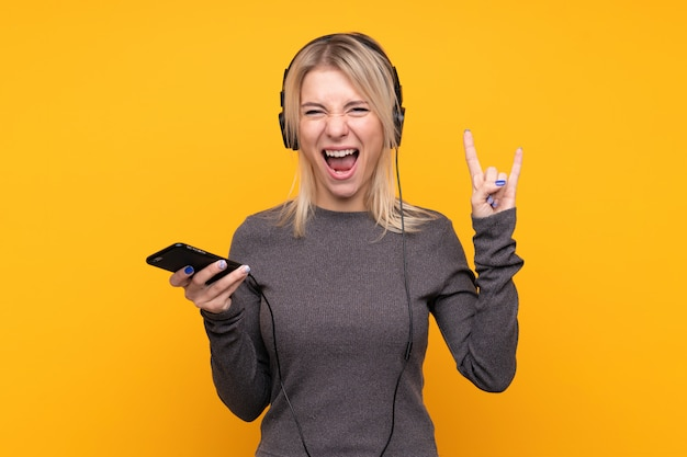 Young blonde woman over isolated yellow wall listening music with a mobile making rock gesture Premium Photo