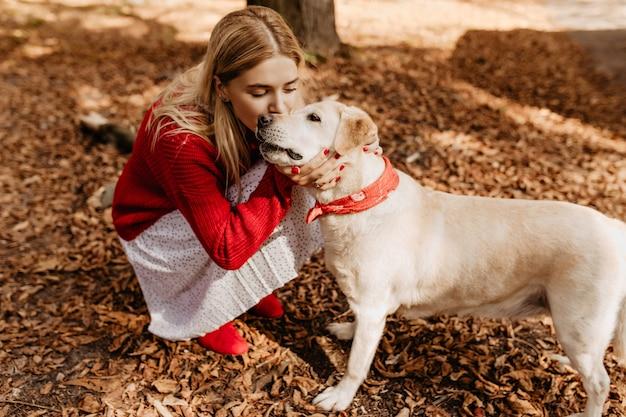 Молодая блондинка целует нежно очаровательную собаку. милая девушка со своим питомцем, сидя среди опавших листьев. Бесплатные Фотографии