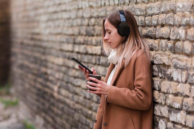 コピースペースとヘッドフォンで音楽を聴く若いブロンドの女性 無料写真