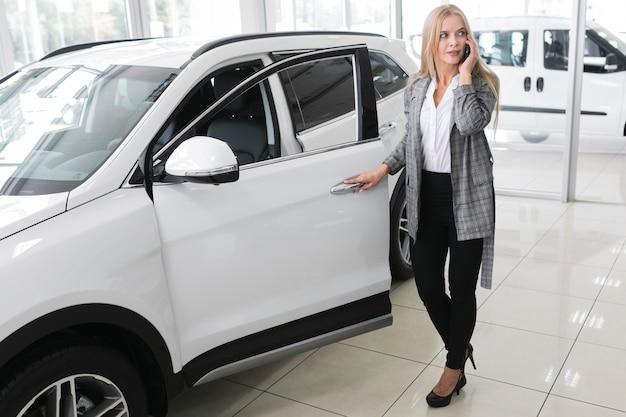 Young blonde woman opening  car door long shot Free Photo