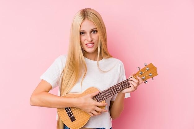 分離されたウクレレを演奏若いブロンドの女性、 Premium写真