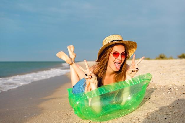 若いブロンドの女性はリラックスして夏休みを楽しんだり、エアマットレスに横になって日光浴をしたり、明るくスタイリッシュなビーチウェアの帽子とサングラスをかけたりします 無料写真