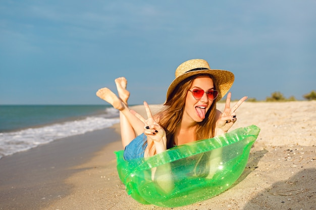 Young blonde woman relax and enjoy her summer vacation, lay on air mattress and getting sunbathe, bright stylish beachwear hat and sunglasses Free Photo