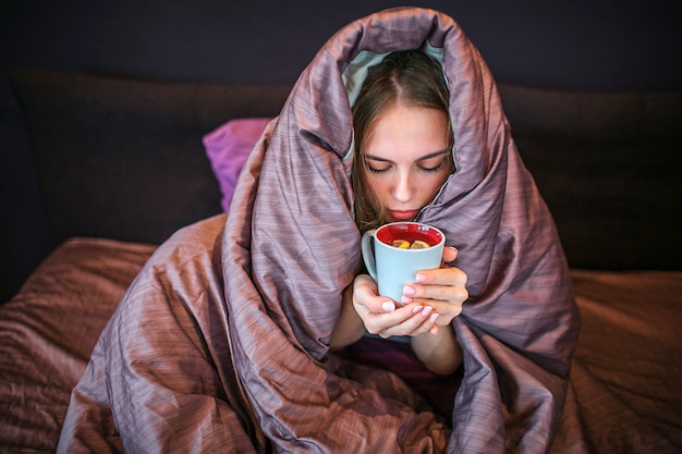 Young blonde woman sits on bed with covered head. she drinks hot tea from cup. woman holds it with both hands and looks down. Premium Photo
