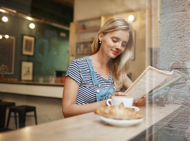 Giovane donna bionda seduta in caffè e lettura Foto Gratuite