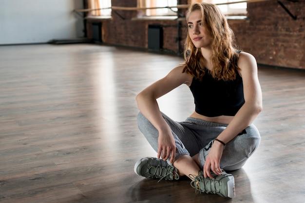 Young blonde woman sitting on hardwood floor Free Photo