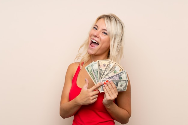 Young blonde woman taking a lot of money Premium Photo