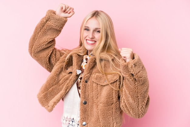 Young blonde woman wearing a coat against a pink wall
