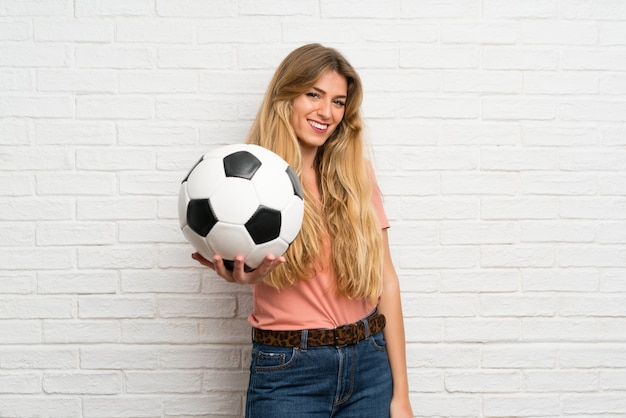 Young blonde woman over white brick wall holding a soccer ball Premium Photo