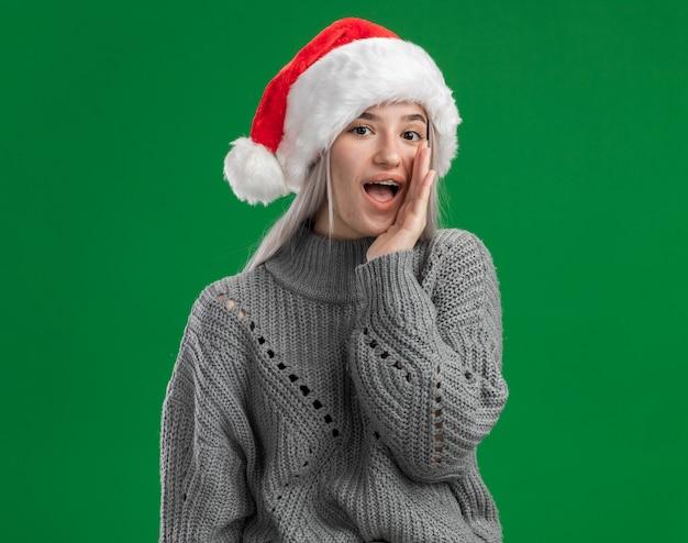 Giovane donna bionda in maglione invernale e cappello santa raccontando un bisbiglio segreto con la mano vicino alla bocca in piedi su sfondo verde Foto Gratuite