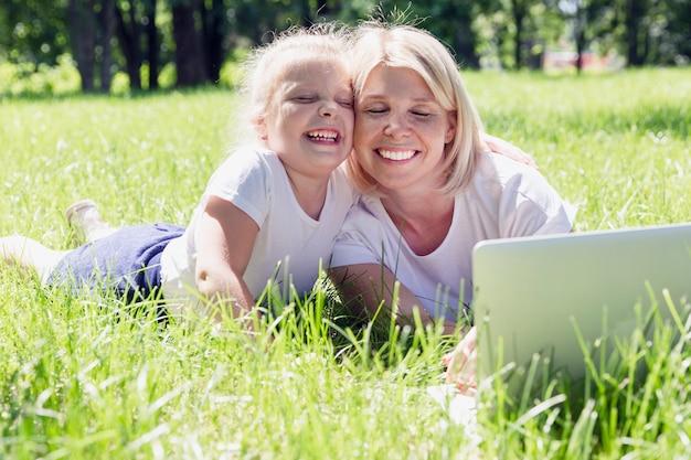小さな娘と若いブロンドの女性はラップトップで公園の芝生に寝転んで、笑って、日当たりの良い夏の日に楽しんでください。 Premium写真