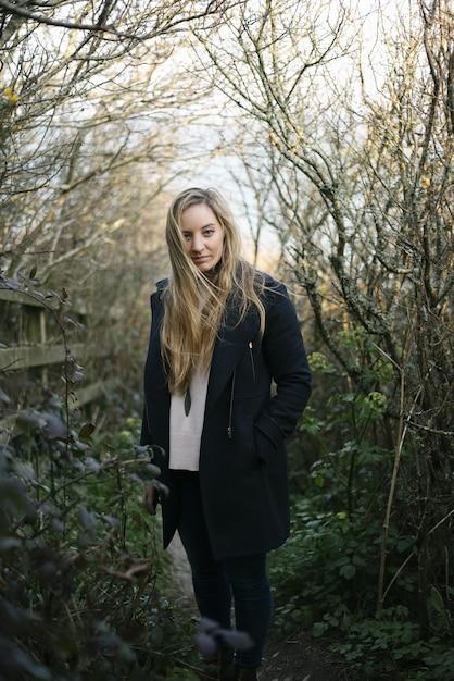 Giovane donna bionda con un mantello nero in piedi su un sentiero circondato da alberi spogli Foto Gratuite
