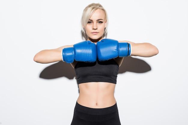 Giovane donna bionda con guantoni da boxe blu pronti a combattere su bianco Foto Gratuite