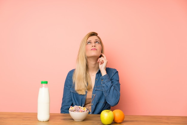 Young blonde woman with bowl of cereals standing and thinking an idea Premium Photo