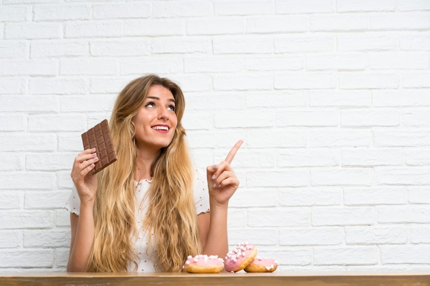 Young blonde woman with chocolat pointing up Premium Photo