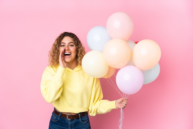 Young blonde woman with curly hair catching many balloons isolated on pink wall shouting with mouth wide open Premium Photo