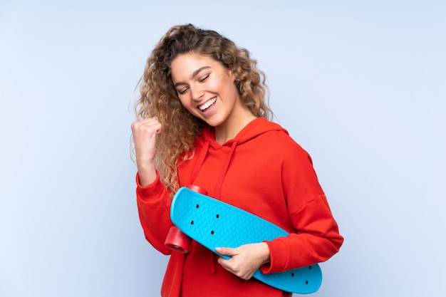 Young blonde woman with curly hair isolated on blue wall with a skate Premium Photo