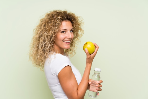 Young blonde woman with curly hair with an apple and with a bottle of water Premium Photo