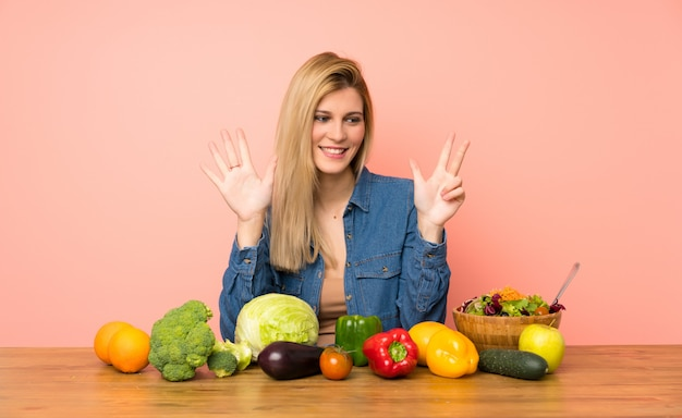 Young blonde woman with many vegetables counting eight with fingers Premium Photo