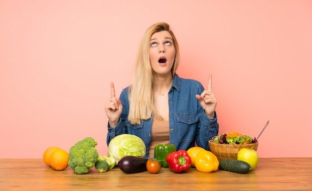 Young blonde woman with many vegetables surprised and pointing up Premium Photo