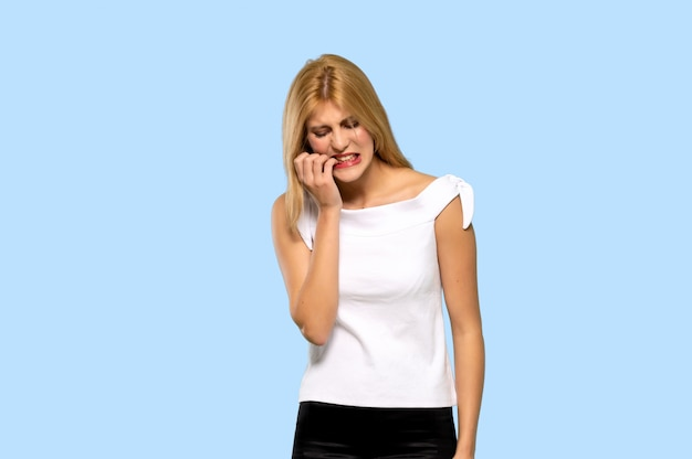 Young blonde woman with toothache on isolated blue background Premium Photo