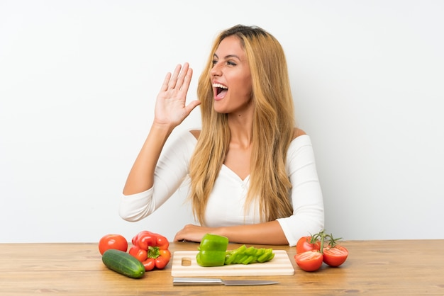 Young blonde woman with vegetables in a table shouting with mouth wide open Premium Photo
