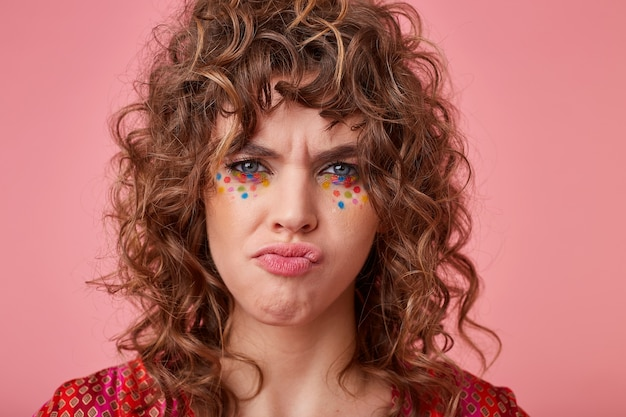 Young blue-eyed woman with brown curly hair and festive makeup looking provocatively and frowning her eyebrows, isolated Free Photo
