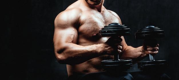Young bodybuilder on a black background Premium Photo