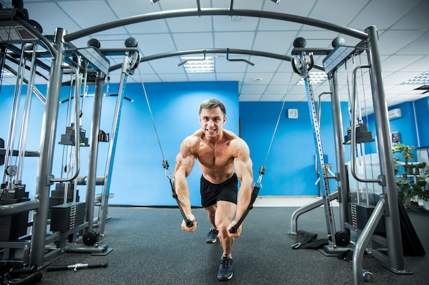 Young bodybuilder is working on his chest with cable crossover in gym Premium Photo