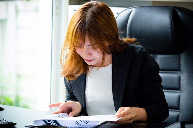 Young boss serious while checking paperwork Free Photo
