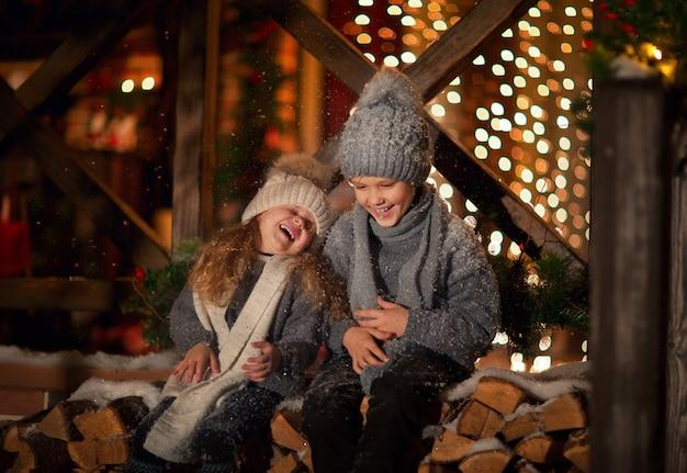 木の家の前に丸太の上に座っている灰色の冬の帽子、セーター、スカーフの少年と少女 Premium写真