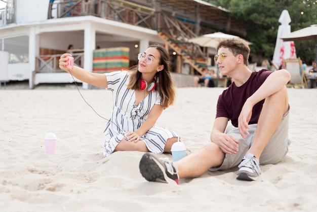 Молодой мальчик и девочка вместе отдохнуть на пляже Бесплатные Фотографии