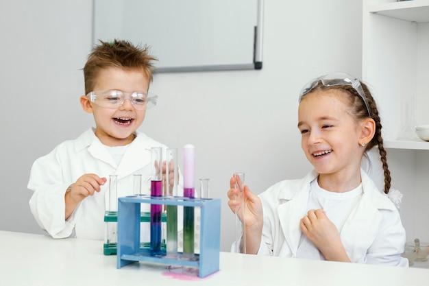 実験室で実験を楽しんでいる少年と少女の科学者 無料写真
