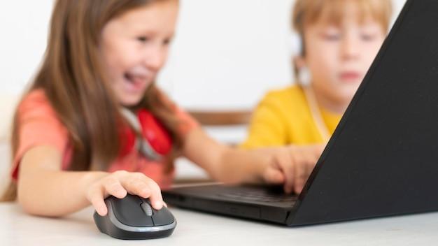 Молодой мальчик и девочка с помощью ноутбука и мыши Бесплатные Фотографии