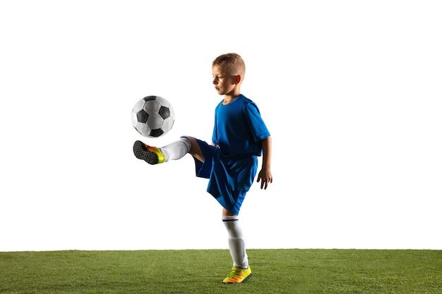 白のゴールのためにフェイントまたはボールでキックをするスポーツウェアのサッカーまたはフットボール選手としての少年。 無料写真