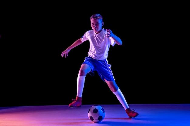 Молодой мальчик как футболист или футболист на темной стене студии Бесплатные Фотографии