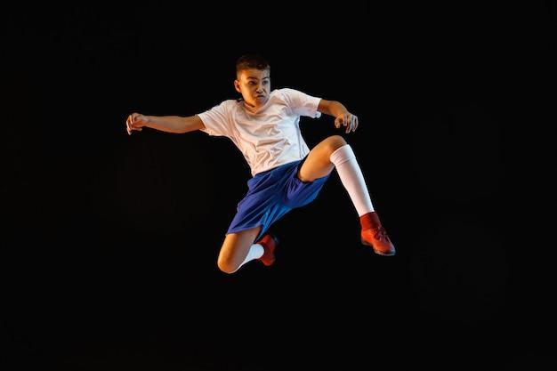 暗い壁にサッカーやサッカー選手としての少年 無料写真