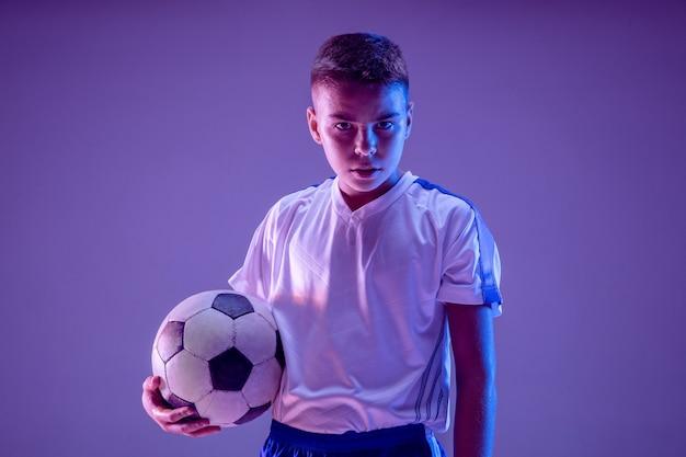 Мальчик как футболист или футболист на темной стене Бесплатные Фотографии