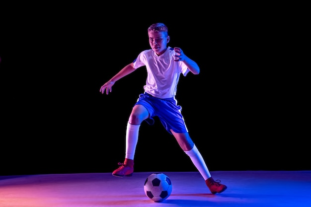 Young boy as a soccer or football player on dark studio wall Free Photo