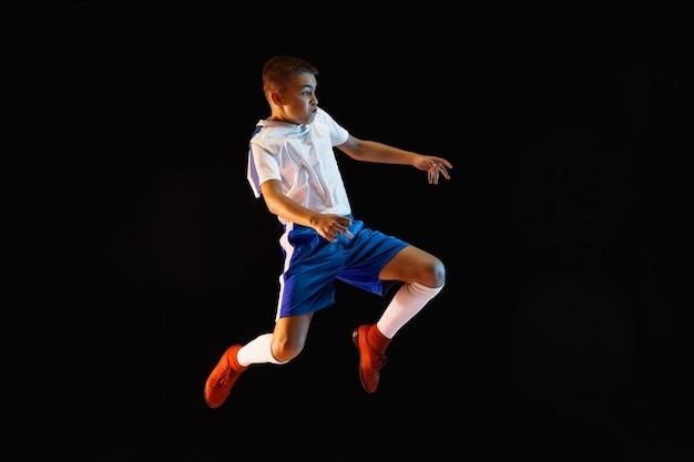 Ragazzo giovane come un giocatore di calcio o di football sulla parete scura Foto Gratuite