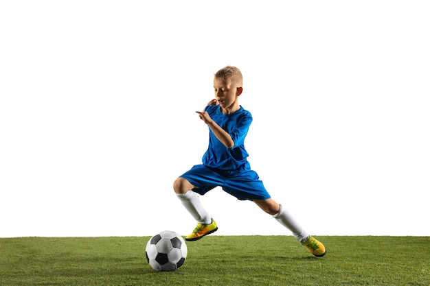 Young boy as a soccer or football player in sportwear making a feint or a kick with the ball for a goal on white. Free Photo