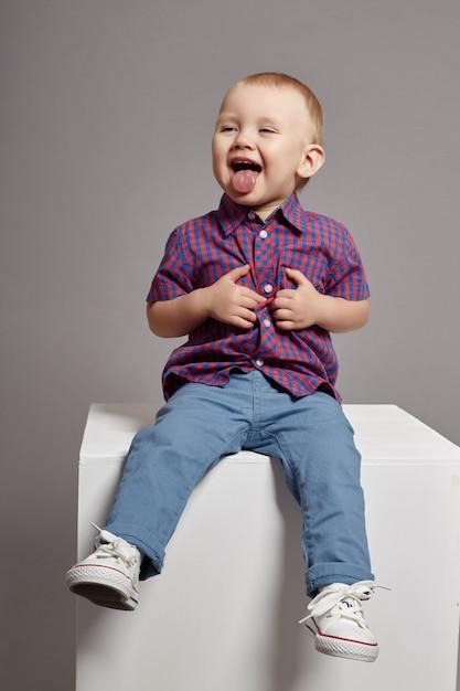 Young boy child smiling sitting on white cube Premium Photo