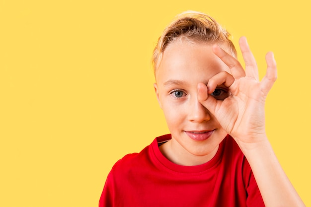 Young boy covering eye with ok sign Free Photo