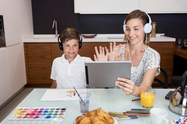 Giovane ragazzo che fa videoconferenza insieme alla madre Foto Gratuite