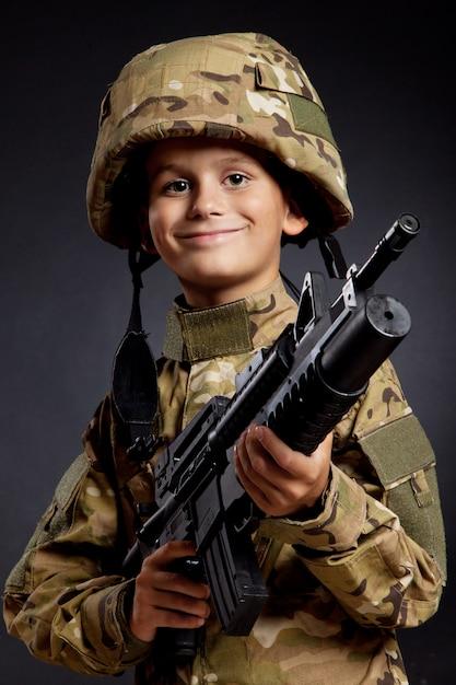 Молодой мальчик одет как солдат с винтовкой Premium Фотографии