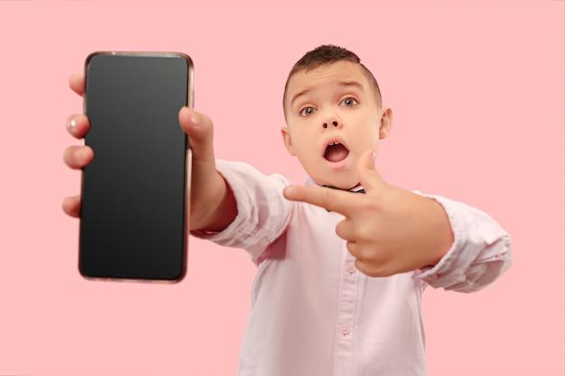 Giovane ragazzo che tiene smartphone in bianco Foto Gratuite