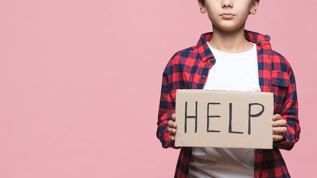 Young boy holding cardboard with help message Free Photo