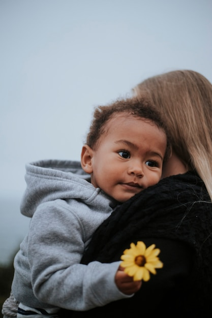 Young boy holding a flower carried by his mom Premium Photo