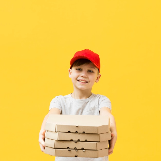Young boy holding pizzas boxes Free Photo