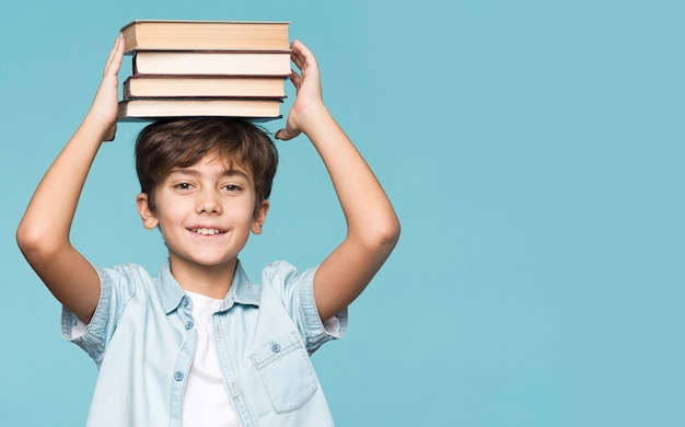Young boy holding stack of books on head Free Photo